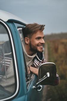No meio do nada. jovem bonito inclinando-se para fora da janela da van e sorrindo enquanto está sentado no banco do passageiro da frente