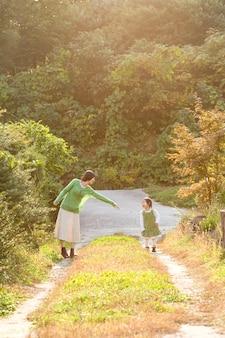No parque ao pôr do sol, a mãe e a criança se divertem.