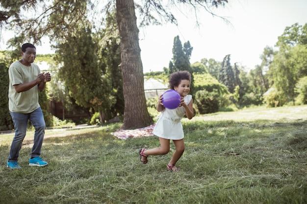 No parque. homem e sua linda filha jogando bola no parque
