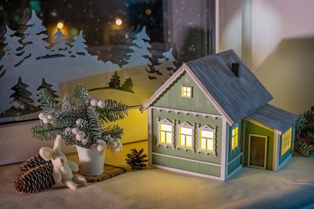 No peitoril da janela, entre os enfeites da árvore de natal, brilha uma lamparina em forma de casa de aldeia como janela de neve noturna e enfeites de papel.