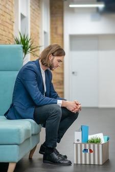 No perfil, jovem e triste trabalhador de escritório de terno sentado no corredor com pertences pessoais