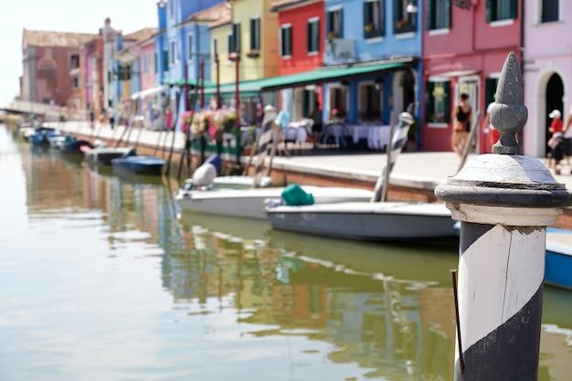 No primeiro plano, um poste pintado com listras pretas e brancas no fundo (fora de foco) as casas coloridas e um canal da ilha de burano, em veneza, itália.