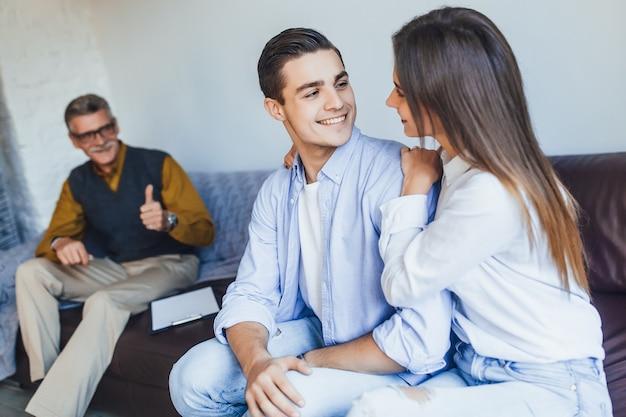 No psicólogo. lindo casal jovem está sentado no sofá e se abraçando enquanto o médico faz anotações