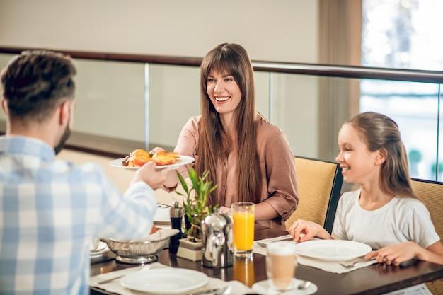 No restaurante. homem dando um prato com comida para sua esposa sorridente