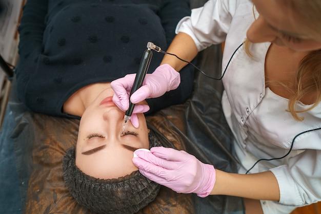 No salão de beleza no cliente feliz bonito do artista do tatuagem.