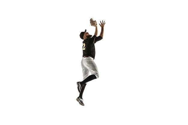 No salto. jogador de beisebol, lançador em uniforme preto praticando e treinando isolado na parede branca. jovem desportista profissional em ação e movimento. estilo de vida saudável, esporte, conceito de movimento.