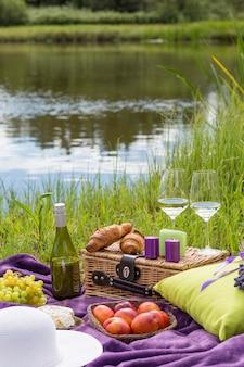 No tapete roxo encontra-se um travesseiro, um buquê de lavanda, uma garrafa de vinho, croissants