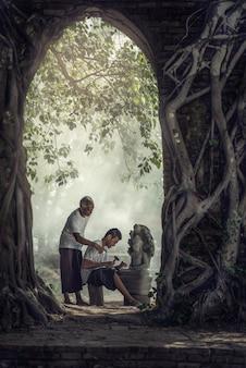 No treinamento de trabalho; escultor de pedra, tailândia