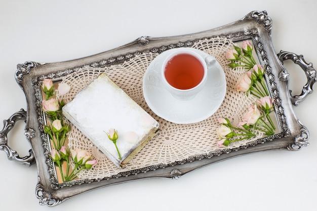 No velho guardanapo de laço de bandeja de prata, botões de rosa, uma xícara de chá e um livro
