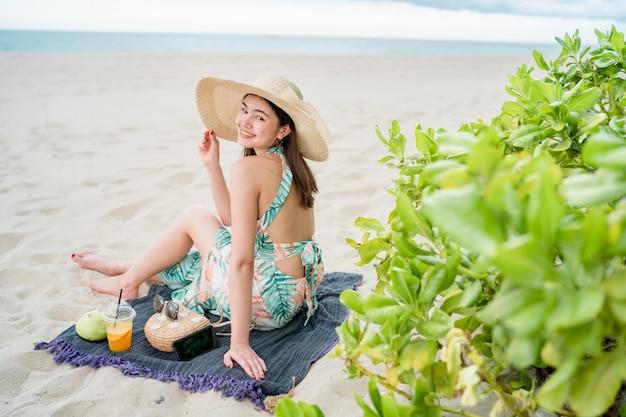 No verão, mulher bonita asiática usando um vestido está sentado e tocar um telefone inteligente