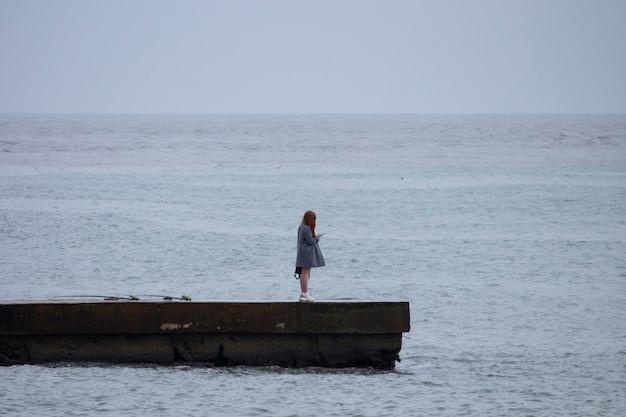 No verão, uma garota de cabelo comprido fica em pé no cais, olhando para a câmera.