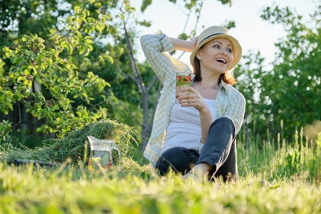 No verão, uma jardineira de chapéu sentada na grama recém-cortada