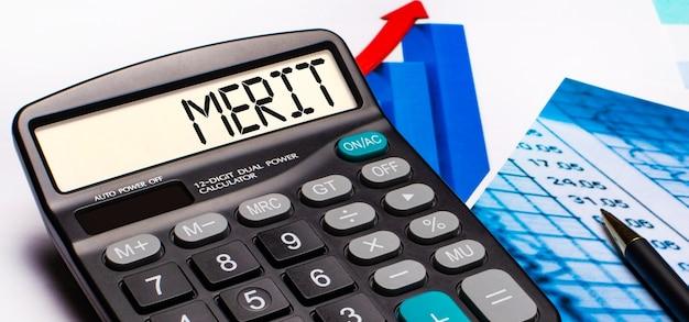 No visor da calculadora, há uma inscrição merit. perto estão diagramas e gráficos coloridos. conceito de negócios