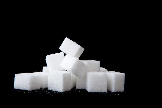 Nódulos de açúcar empilhados juntos contra um fundo preto