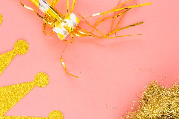 Noisemaker e coroa perto do ouropel dourado