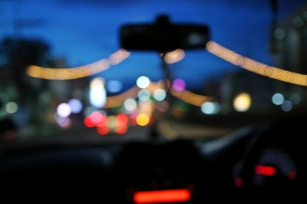 Noite abstrata do bokeh no carro no fundo da estrada.