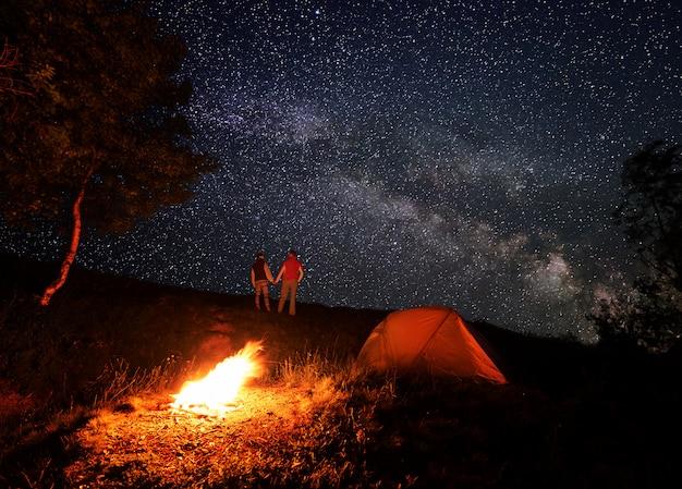 Noite acampando com uma fogueira e barraca sob um céu estrelado e a via láctea. turistas de homem e mulher estão de mãos dadas e se olhando sob o céu romântico nas montanhas