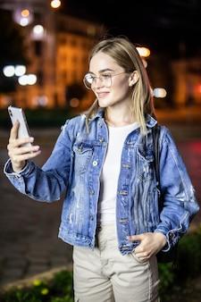 Noite ao ar livre da jovem mulher usando a cara do telefone inteligente iluminada pelo screenlight. internet, rede social, conceito de tecnologia