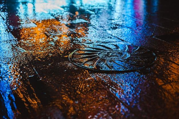 Noite chuvosa em uma cidade grande, reflexo das luzes coloridas da cidade na superfície da estrada molhada.