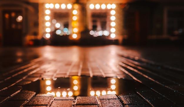 Noite chuvosa em uma cidade grande, reflexos das luzes na superfície da estrada molhada.