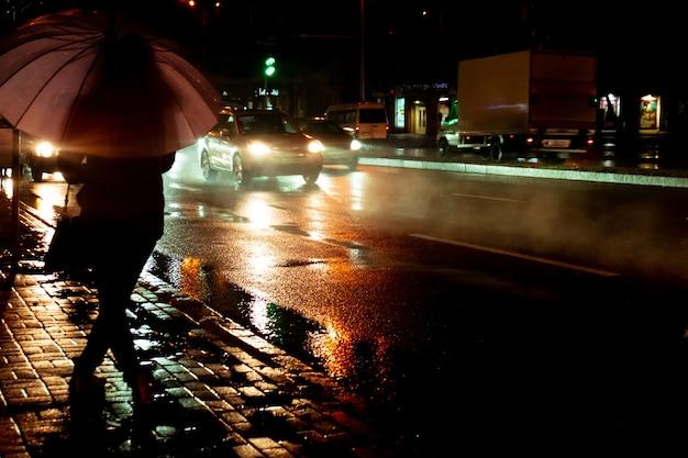 Noite chuvosa, uma silhueta de mulher com guarda-chuva e tráfego intenso com gotas de chuva, tempo de outono