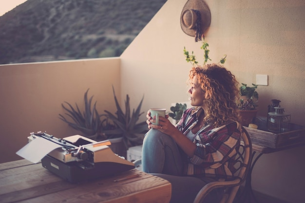 Noite com luz adorável e linda mulher solitária tomando e bebendo um chá com a velha máquina de escrever sem tecnologia na frente da mesa