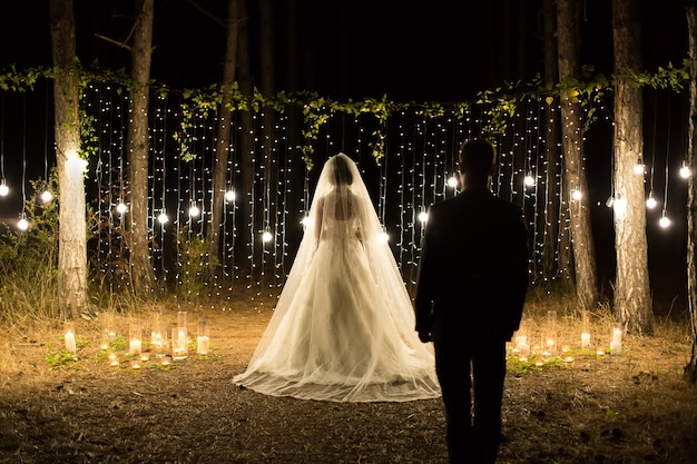 Noite da cerimônia de casamento. encontro dos noivos, a noiva e o noivo na floresta de pinheiros de coníferas de velas e lâmpadas.