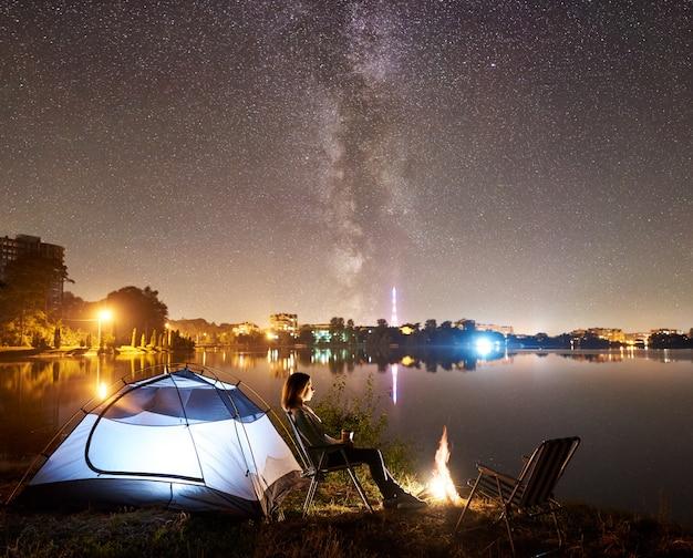 Noite de acampamento na margem do lago perto da fogueira, barraca do turista
