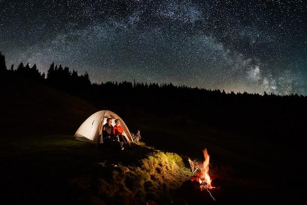 Noite de acampamento nas montanhas. os turistas do casal descansam na tenda iluminada perto da fogueira sob o lindo céu noturno cheio de estrelas e via láctea