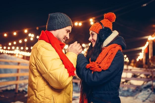 Noite de inverno, amor casal mãos quentes ao ar livre