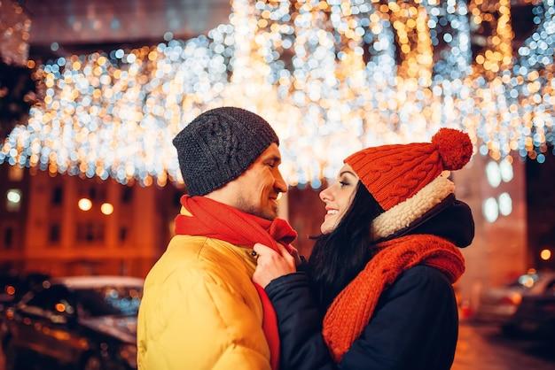 Noite de inverno, amor casal se abraça na rua
