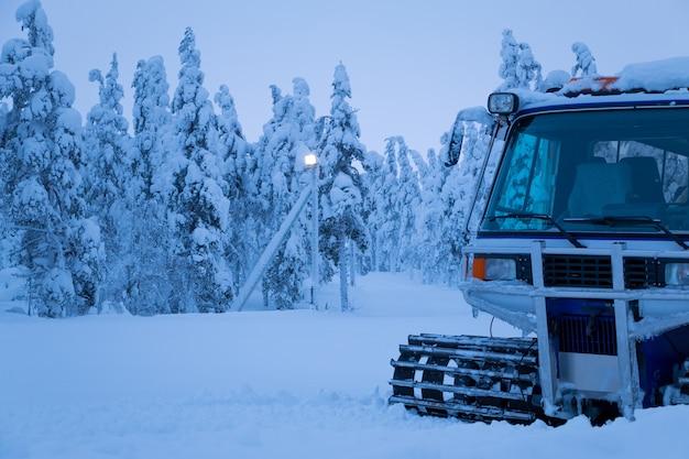 Noite de inverno. as árvores deixavam cair galhos sob o peso de grandes camadas de neve. snowcat na orla da floresta