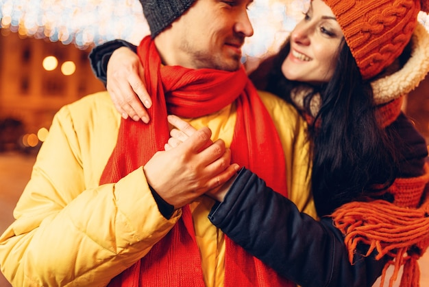 Noite de inverno, casal apaixonado e sorridente se abraçando na rua
