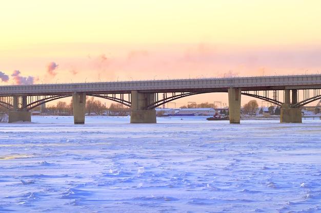 Noite de inverno no ob. as pontes municipais e metropolitanas cruzam um largo rio, coberto de gelo