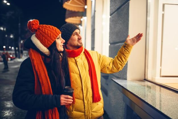 Noite de inverno urbano, amor casal olhando na vitrine. homem e mulher tendo um encontro romântico na rua da cidade