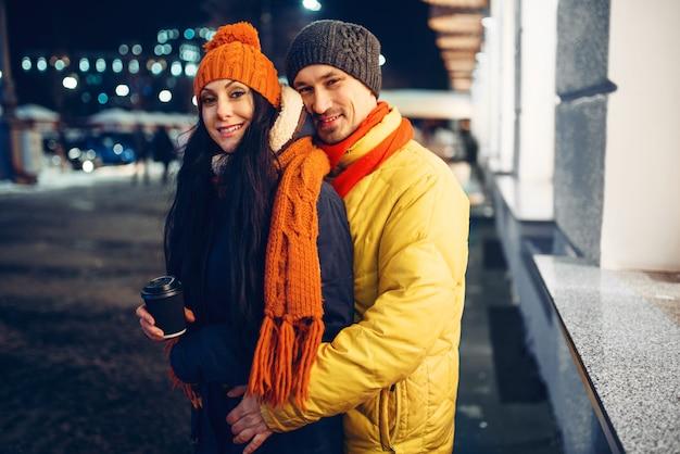 Noite de inverno urbano, retrato de casal amor ao ar livre. homem e mulher tendo um encontro romântico na rua da cidade