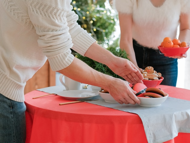Noite de natal. casal definindo mesa festiva com tangerinas e biscoitos de gengibre na cozinha de casa.
