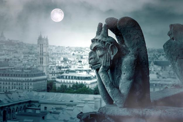 Noite de nevoeiro e luz da lua sobre as gárgulas de notre dame em paris