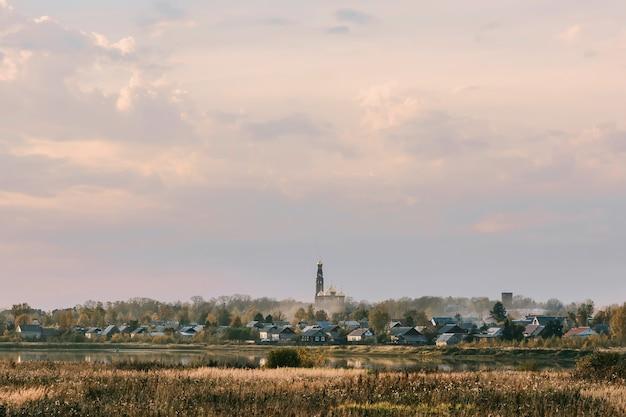 Noite de outono paisagem com um campo e um rio e uma igreja cristã no horizonte