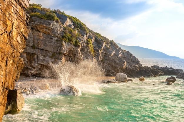 Noite de verão e a pequena praia em uma costa rochosa. spray de surf do mar