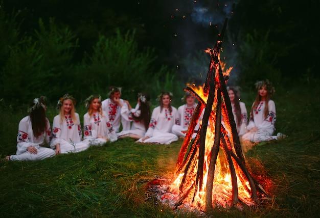 Noite de verão, jovens em roupas eslavas, sentados perto da fogueira.