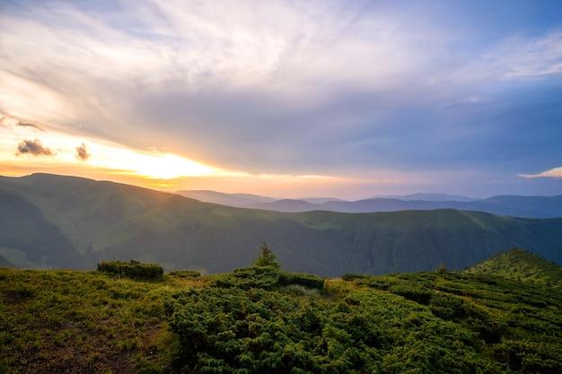 Noite de verão paisagem montanhosa com colinas gramadas e picos distantes ao pôr do sol colorido.
