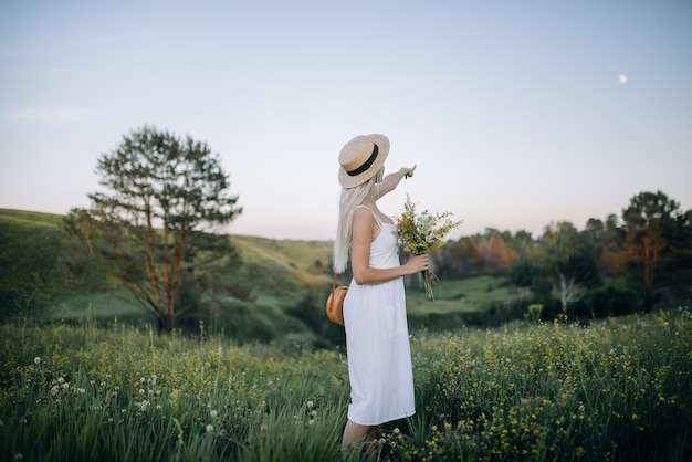 Noite de verão. uma jovem garota com um vestido branco e um chapéu de palha fica em uma bela encosta e aponta para a lua. maravilhoso horário de verão