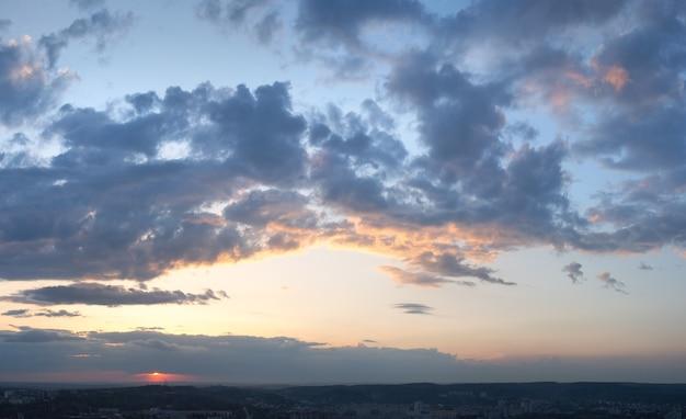Noite do céu do sol com nuvens acima da vista da cidade de lviv (ucrânia, vista da colina de lvov