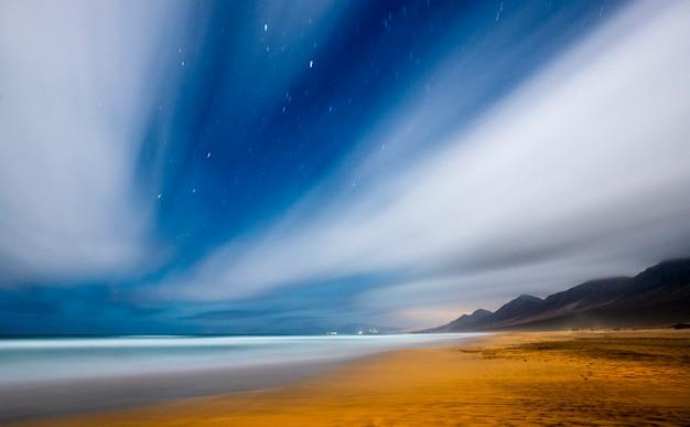 Noite filmada na praia com céu azul e estrelas