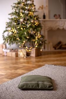 Noite interior de ano novo com almofada verde macia no chão, primeiro plano e árvore de natal com guirlandas brilhantes e lareira branca no fundo. vertical
