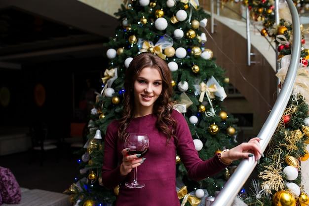 Noite mágica de natal. mulher bonita em vestido de noite com um copo de vinho celebra o natal