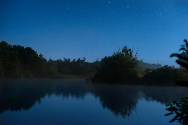 Noite no lago com água azul escura e estrelas no céu