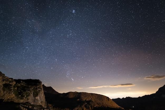 Noite nos alpes sob o céu estrelado e as majestosas falésias rochosas nos alpes italianos