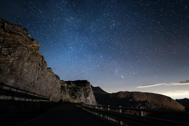 Noite nos alpes sob o céu estrelado e os penhascos rochosos majestosos nos alpes italianos, com constelação de orion no horizonte.